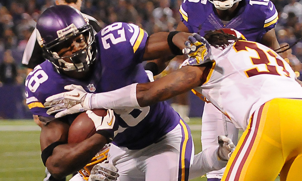 . Minnesota running back Adrian Peterson tries to break the tackle of Washington strong safety Brandon Meriweather in the second quarter. (Pioneer Press: John Autey)