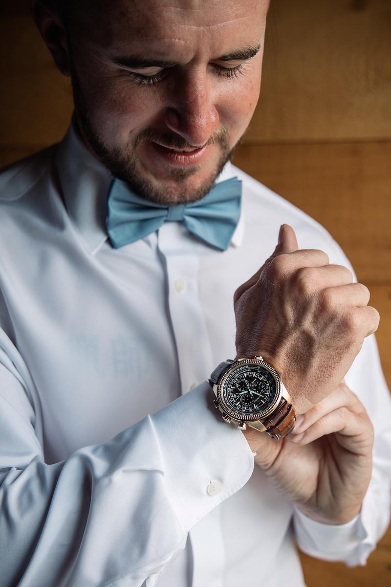 a close up photo of a groom putting on his watch before his wedding