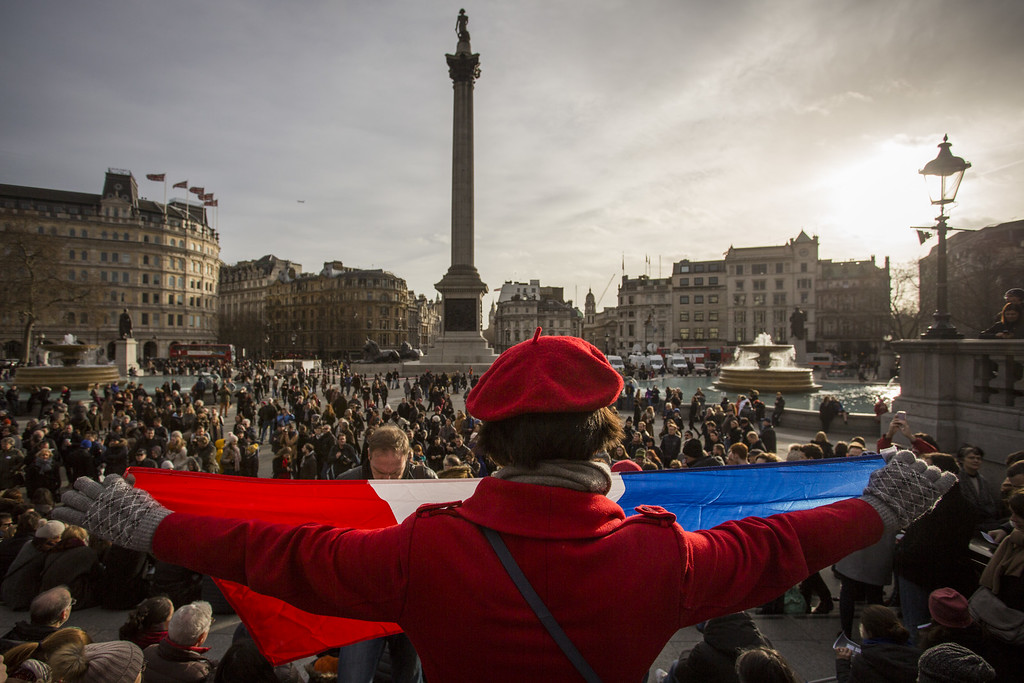 . LONDON, ENGLAND - JANUARY 11:  A woman holds the national flag of France as people gather in Trafalgar Square to show their respect to victims of the terrorist attacks in Paris on January 11, 2015 in London, England.  London landmarks including Tower Bridge, Trafalgar Square and the National Gallery are to be lit in the blue, white and red colours of the French national flag later today in tribute to the 17 people killed in the Paris terror attacks. The terrorist atrocities started on Wednesday with the attack on the French satirical magazine Charlie Hebdo, killing 12, and ended on Friday with sieges at a printing company in Dammartin en Goele and a Kosher supermarket in Paris with four hostages and three suspects being killed. A fourth suspect, Hayat Boumeddiene, 26, escaped and is wanted in connection with the murder of a policewoman.  (Photo by Rob Stothard/Getty Images)