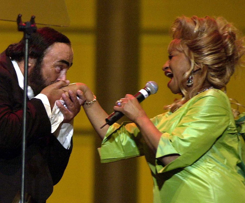 . Italian tenor Luciano Pavarotti kisses the hand of Cuban singer Celia Cruz during the Pavarotti & friends 2001 annual charity concert at the Parco Novi Sad in Modena, Italy, Tuesday, May 29, 2001. (AP Photo/Luca Bruno)