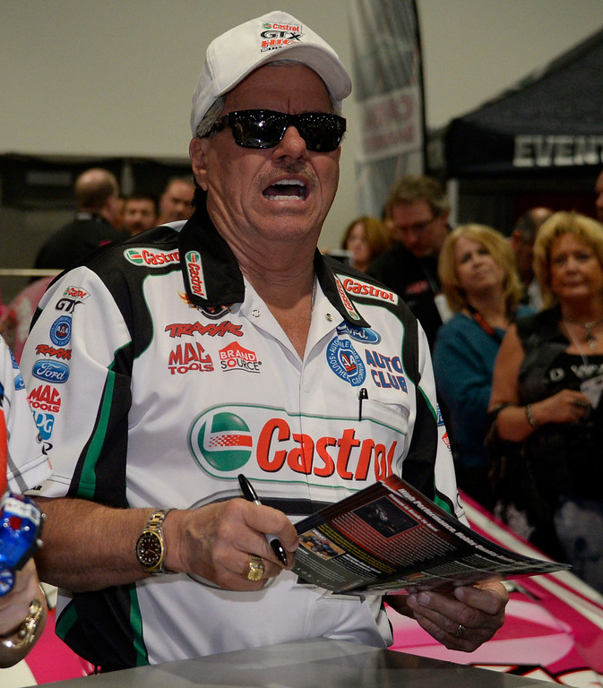 . Nov 5,2013 Las Vegas NV. USA. NHRA Funny Car Champion John Force signs autographs at the traxxas booth during the first day of the 2013 SEMA auto show.