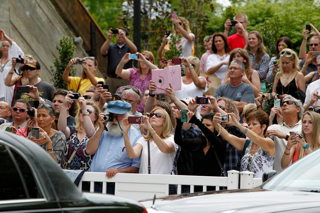 . People paying their last respects to country music legend George Jones take photographs as his casket is removed during a public memorial service at the Grand Ole Opry House in Nashville, Tennessee, May 2, 2013.  REUTERS/Harrison McClary