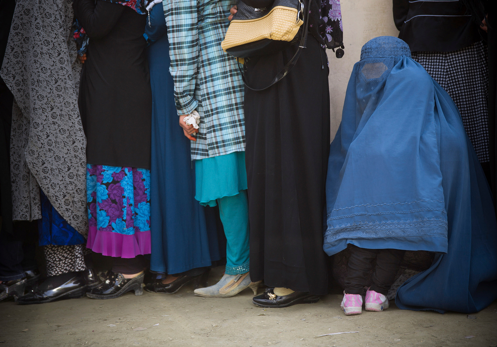 . A child hides under his mother\'s burqa as women queue to get their registration card on the last day of voter registration for the upcoming presidential elections outside a school in Kabul, Afghanistan, Tuesday, April 1, 2014. Elections will take place on April 5, 2014. (AP Photo/Anja Niedringhaus)