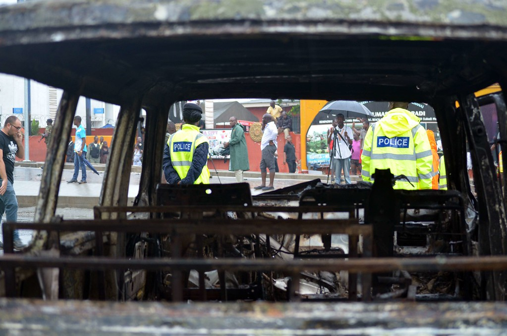. Rescuers and officials stand next to a charred vehicle at the burnt-out petrol station where over 90 people were killed in a fire in Accra, on June 4, 2015. The fire broke out at the filling station in the Kwame Nkrumah Circle area of the city late on Wednesday night and is thought to have spread from a nearby residence. AFP PHOTO / FATI  BRAIMAH/AFP/Getty Images