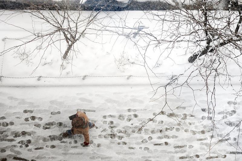 . A man walks through the snow on E. Liberty St. in downtown Ann Arbor, Mich. on Wednesday, Dec. 26, 2012. (AP Photo/AnnAbor.Com, Melanie Maxwell)