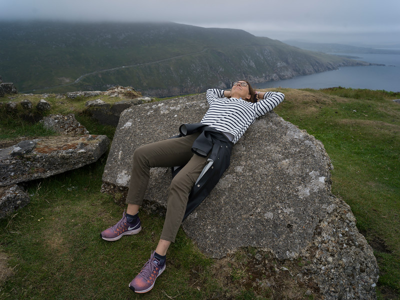 Woman resting back on a rock at Achill Island, County Mayo, Ireland