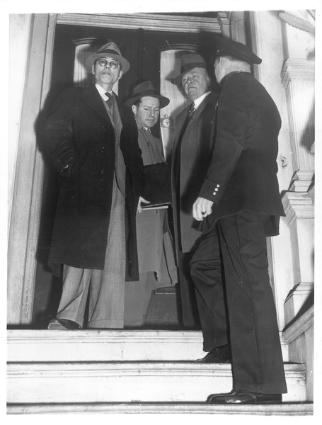 """""""Japanese roundup --  Many Japanese taken into custody in F.B.I. and police roundup.  Photo shows Jitsuzo Ishidu (left) taken in custody, F.B.I. Agent in center, Police Inspector Leo Bunner and Officer Ray Peyre at right.""""--caption on photograph"""