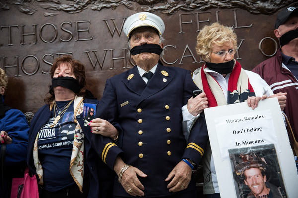 . Al Santora (C), father of Christopher Santora, a victim of the September 11, 2001 attack, and other victim\'s family members protest the decision by city officials to keep unidentified human remains of the 9-11 victims at the 9-11 Museum at the World Trade Center site, on May 10, 2014 in New York City. The decision by city officials to keep the remains at the museum until they are able to be identified has drawn both support and criticism by families of victims. The remains were moved early this morning from the medical examiner\'s repository to the 9-11 Museum.  (Photo by Andrew Burton/Getty Images)