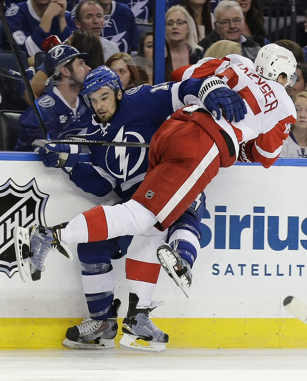 . Detroit Red Wings defenseman Danny DeKeyser (65) hits Tampa Bay Lightning center Cedric Paquette (13) during the second period of Game 7 of a first-round NHL Stanley Cup hockey playoff series Wednesday, April 29, 2015, in Tampa, Fla. (AP Photo/Chris O\'Meara)