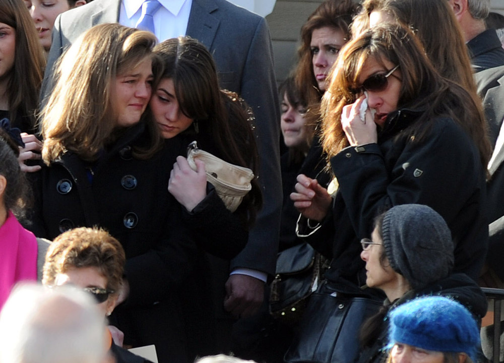 Description of . Mourners exit St. Mary Of The Assumption Church in Katonah, N.Y. after the funeral for Anne Marie Murphy on Thursday, Dec. 20, 2012.  Murphy was killed when Adam Lanza, walked into Sandy Hook Elementary School in Newtown, Conn., Dec. 14, and opened fire, killing 26, including 20 children, before killing himself. (AP Photo/The Stamford Advocate, Lindsay Niegelberg)