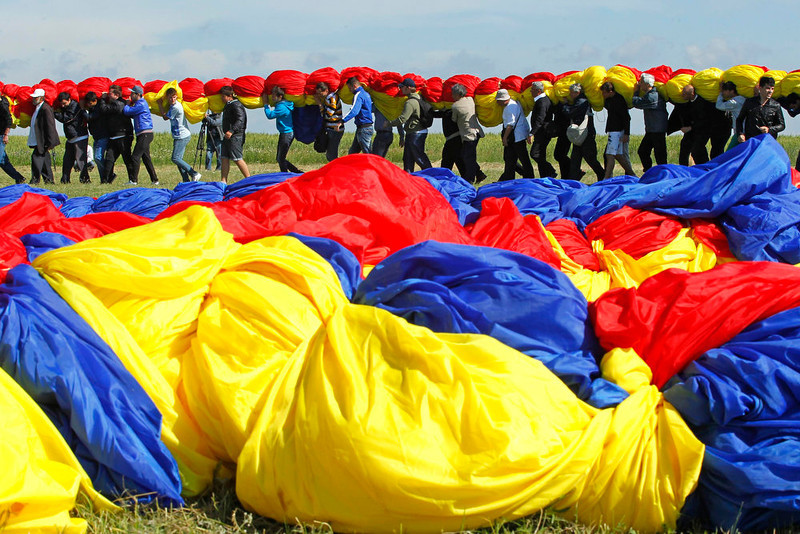 . Workers carry Romania\'s national flag during a Guinness World Record attempt for the world\'s biggest national flag in Clinceni, near Bucharest May 27, 2013. The flag, measuring 349.4 per 226.9 meters, established a new Guinness World Record, according to the organisation\'s officials. REUTERS/Bogdan Cristel