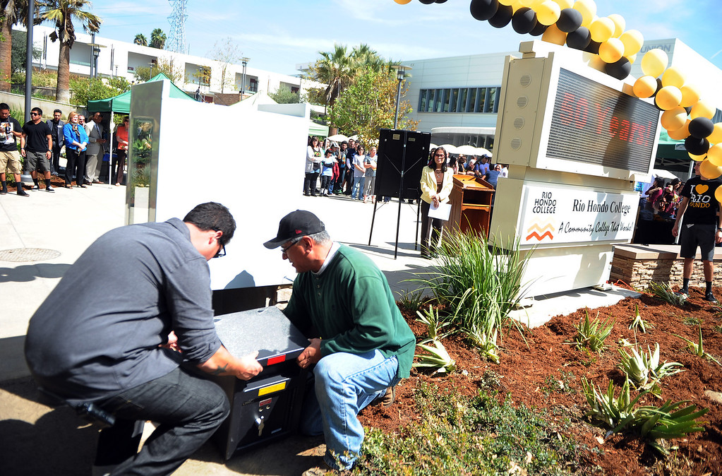 . Christopher Vasquez, left, with Gaspar Sopelo bury the capsule during a celebration of the colleges 50th anniversary with a time capsule burial, cake and signing of a giant birthday card at Rio Hondo College on Thursday, March 14, 2013 in Whittier, Calif.  (Keith Birmingham Pasadena Star-News)