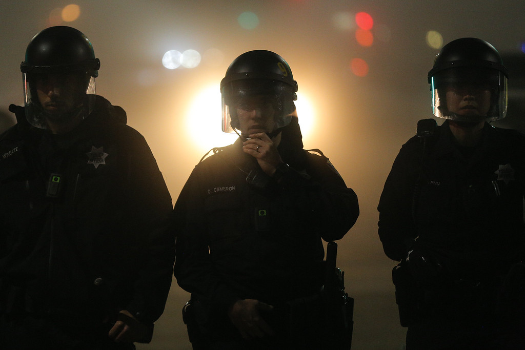 . Police officers wearing body cameras form a line in East Oakland on the second night of demonstrations following a Staten Island, New York grand jury\'s decision not to indict a police officer in the chokehold death of Eric Garner on December 4, 2014 in Oakland, California. The grand jury declined to indict New York City Police Officer Daniel Pantaleo in Garner\'s death. (Photo by Elijah Nouvelage/Getty Images)