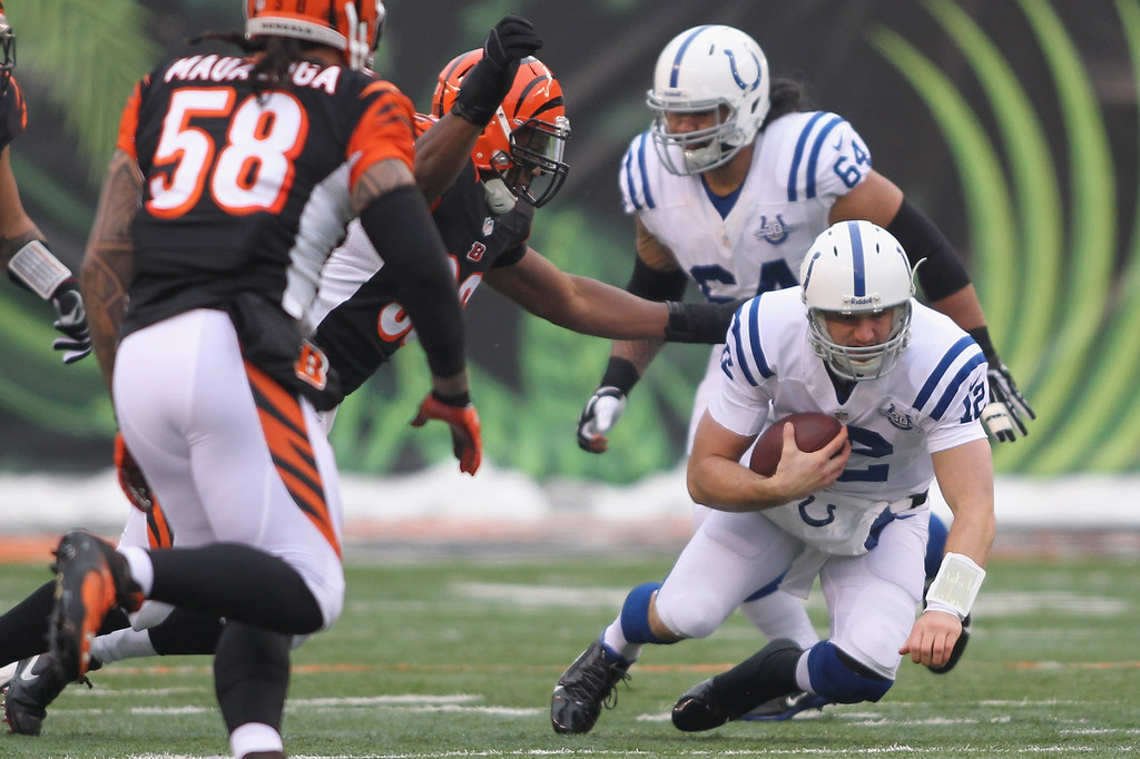 . Andrew Luck #12 of the Indianapolis Colts runs the ball upfield against the pressure of Carlos Dunlap #96 of the Cincinnati Bengals during their game at Paul Brown Stadium on December 8, 2013 in Cincinnati, Ohio.  (Photo by John Grieshop/Getty Images)