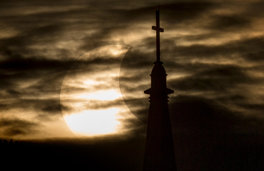 . A break in the clouds reveals a partial solar eclipse behind the University of Notre Dame\'s Basilica of the Sacred Heart, Thursday, Oct. 23, 2014, in South Bend, Ind. (AP Photo/South Bend Tribune, Robert Franklin)