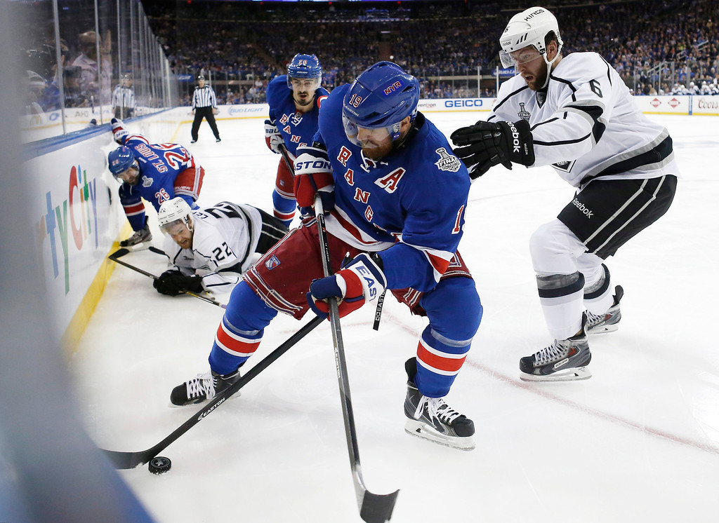 . New York Rangers center Brad Richards, center, seals off the puck from Los Angeles Kings defenseman Jake Muzzin (6), right, in the second period during Game 3 of the NHL hockey Stanley Cup Final, Monday, June 9, 2014, in New York. (AP Photo/Kathy Willens)