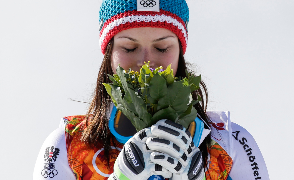 . Women\'s super-G gold medal winner, Austria\'s Anna Fenninger smells her flower bouquet during the flower ceremony on the podium the Sochi 2014 Winter Olympics, Saturday, Feb. 15, 2014, in Krasnaya Polyana, Russia. (AP Photo/GeroBreloer)