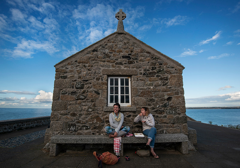 Young women eating fish and chips by an old chapel in the fishing village of St Ives.  Cornwall, England, 2018
