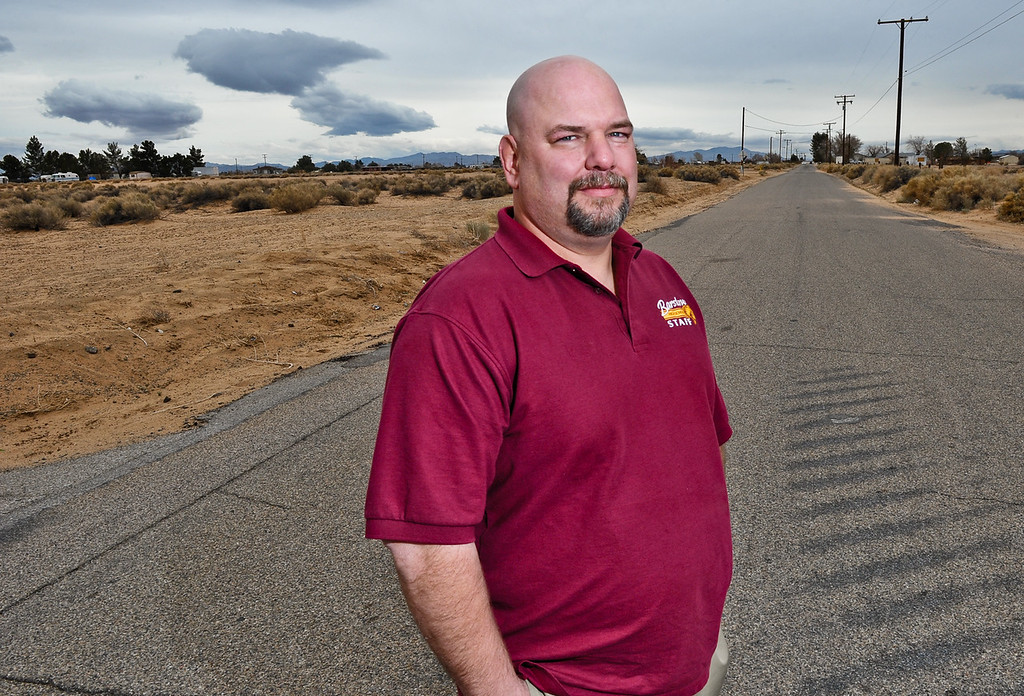 . Barstow High School teacher and Hinkley resident Daron Banks, 44, stands in the middle of a desolate road in Hinkley, Calif. on Thursday, March 7, 2013. Banks is co-chairman of the Community Advisory Committee group that represents the residents\' interest in PG&E related matters. (Rachel Luna / San Bernardino Sun)