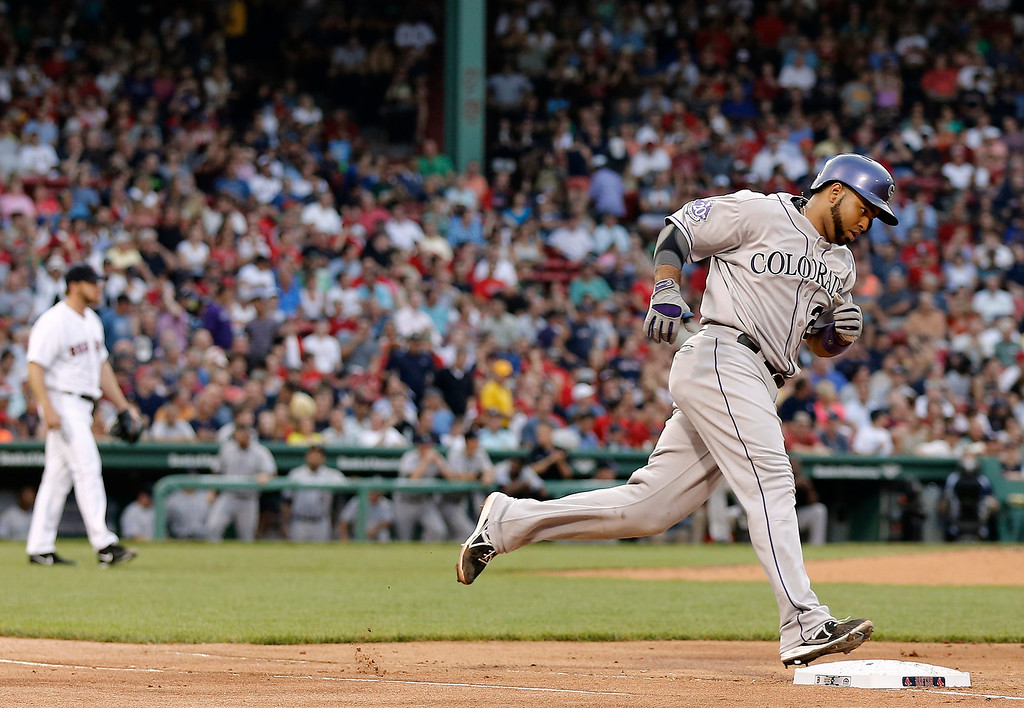 . Colorado Rockies\' Wilin Rosario rounds the bases after hitting a home run off of Boston Red Sox starting pitcher Ryan Dempster, left, during the second inning of a baseball game at Fenway Park in Boston on Tuesday, June 25, 2013. (AP Photo/Winslow Townson)