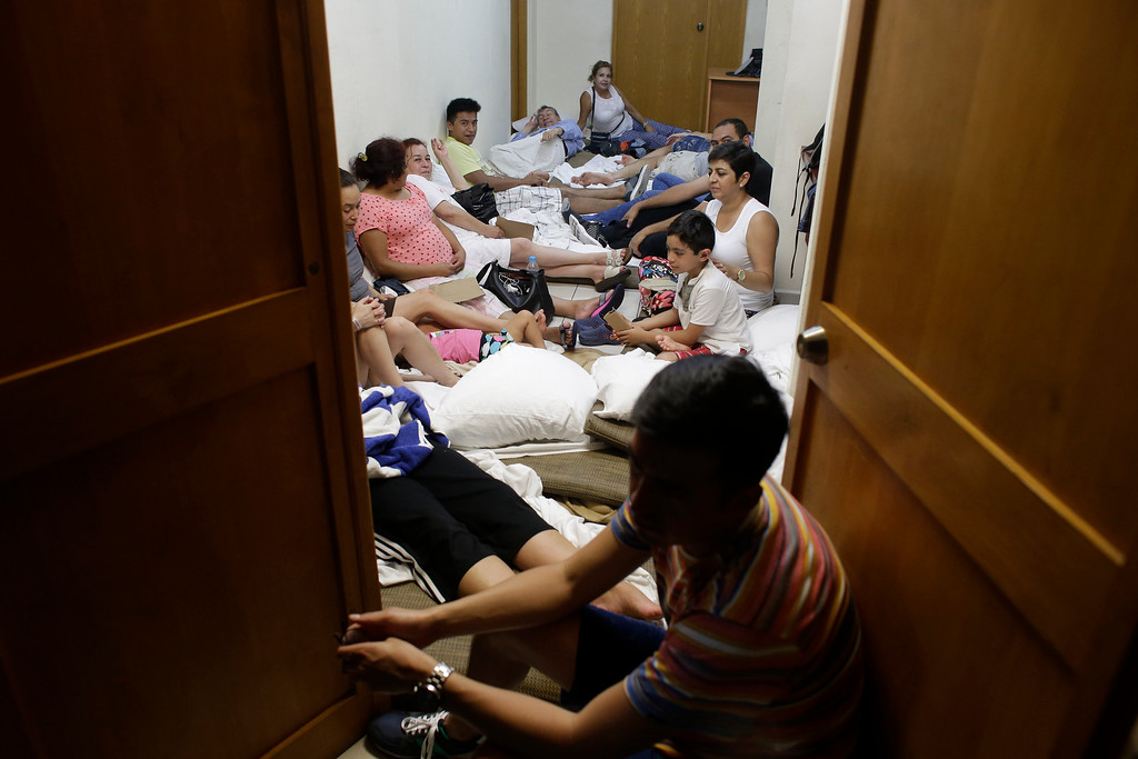 . Tourists rest inside a room in the service area of a resort after the designated area for shelter was destroyed by winds in Los Cabos, Mexico, Monday, Sept. 15, 2014. Hurricane Odile raked the Baja California Peninsula with strong winds and heavy rains early Monday as locals and tourists in the resort area of Los Cabos began to emerge from shelters and assess the damage. (AP Photo/Victor R. Caivano)