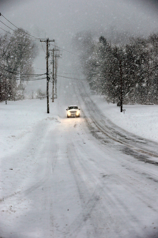 . A car creeps along on a snow-covered rural road near Newtown, Pa., Thursday, Feb. 13, 2014. After pummeling wide swaths of the Southeast, a winter storm dumped more than a foot of snow in parts of the Mid-Atlantic region as it marched Northeast and threatened more power outages, traffic headaches and widespread closures for millions of residents.  (AP Photo/Mel Evans)