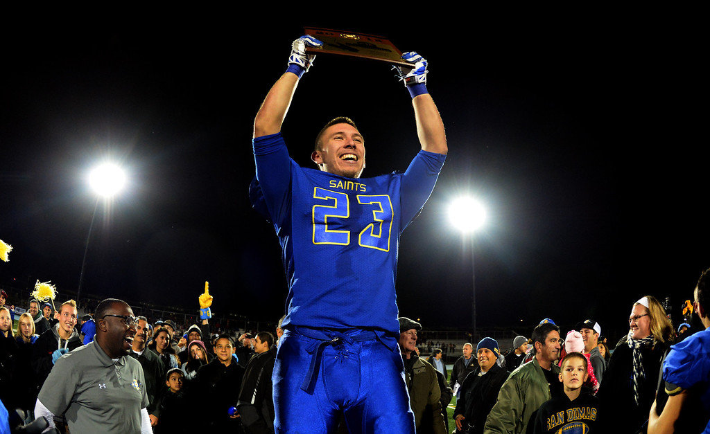 . San Dimas\' Joseph Mayorga (23) hops-up the championship plaque after defeating Paraclete 20-14 a CIF-SS Mid-Valley Division championship football game at San Dimas High School in San Dimas, Calif., on Friday, Dec. 6, 2013.   (Keith Birmingham Pasadena Star-News)