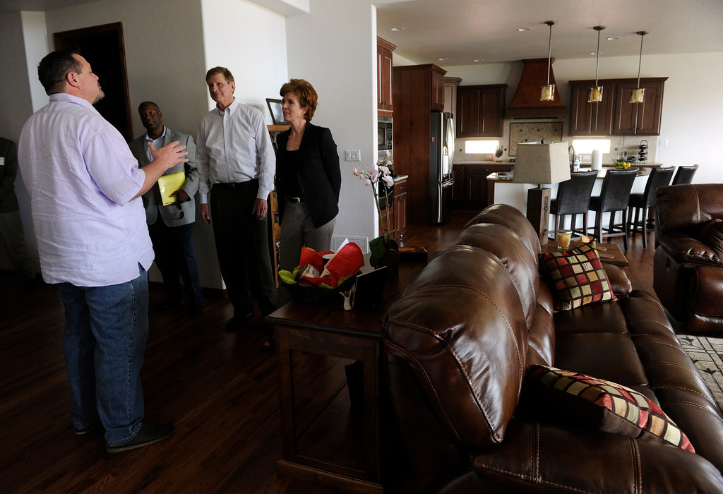 . Kalen Franklin , left, invites the mayor and his wife into his newly built home saying his family was able to rebuild a home they had always wanted. (Photo By Kathryn Scott Osler/The Denver Post)
