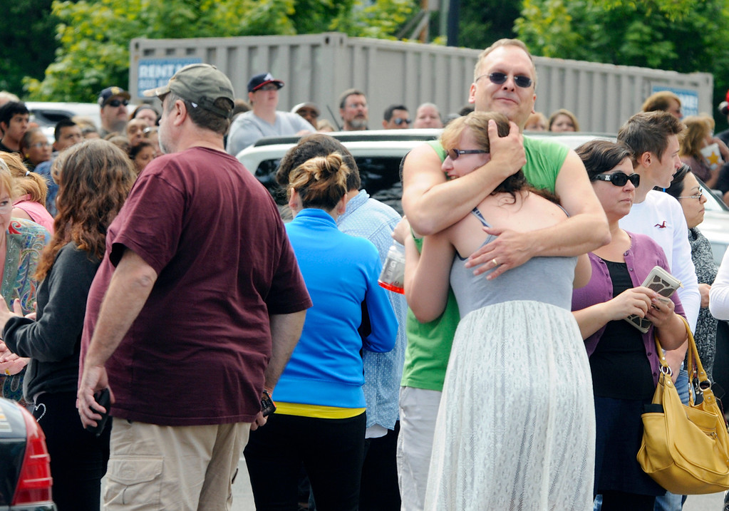 . A family embraces as students arrived at the Fred Meyer grocery store parking lot in Wood Village, Ore., after a shooting at Reynolds High School Tuesday, June 10, 2014, in nearby Troutdale.  (AP Photo/Greg Wahl-Stephens)