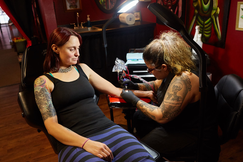 Activity; Art; Buildings; Downtown; Location; Outside; People; Professor; Woman Women; Summer; August; Time/Weather; day; Type of Photography; Portrait; Philosophy Professor Mary Krizan gets a tattoo with Aristotle quote