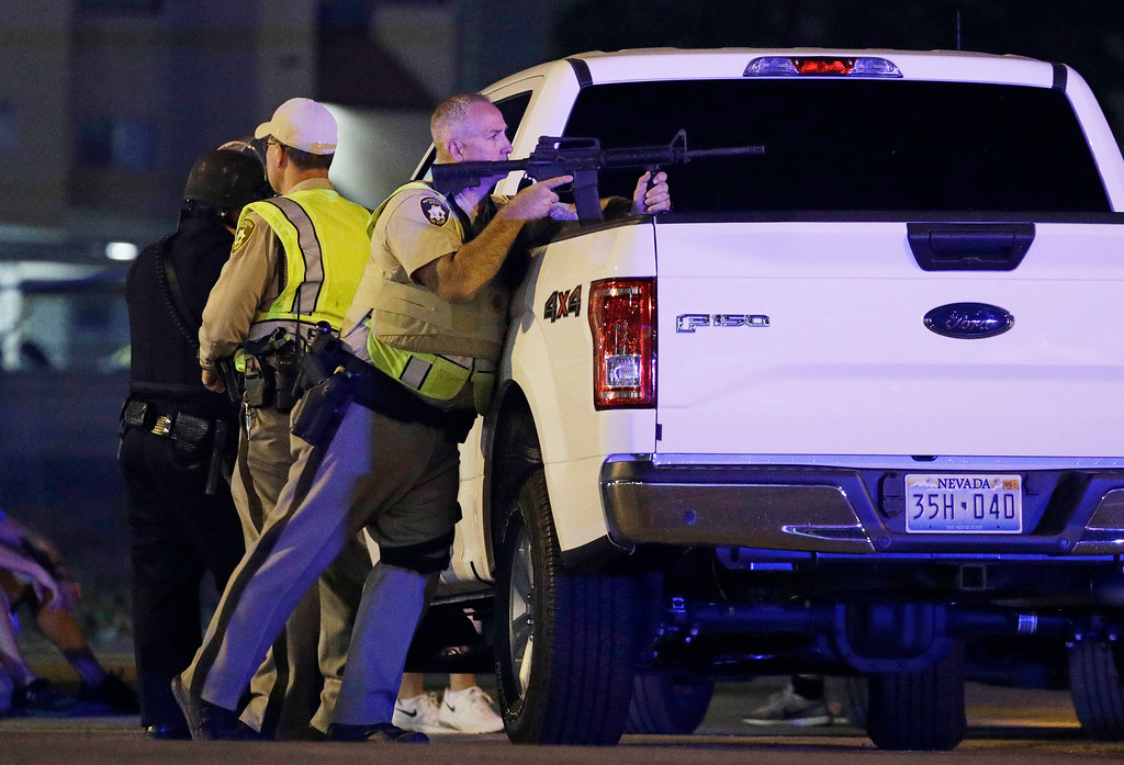 . A police officer takes cover behind a truck at the scene of a shooting near the Mandalay Bay resort and casino on the Las Vegas Strip, Sunday, Oct. 1, 2017, in Las Vegas. Multiple victims were being transported to hospitals after a shooting late Sunday at a music festival on the Las Vegas Strip. (AP Photo/John Locher)