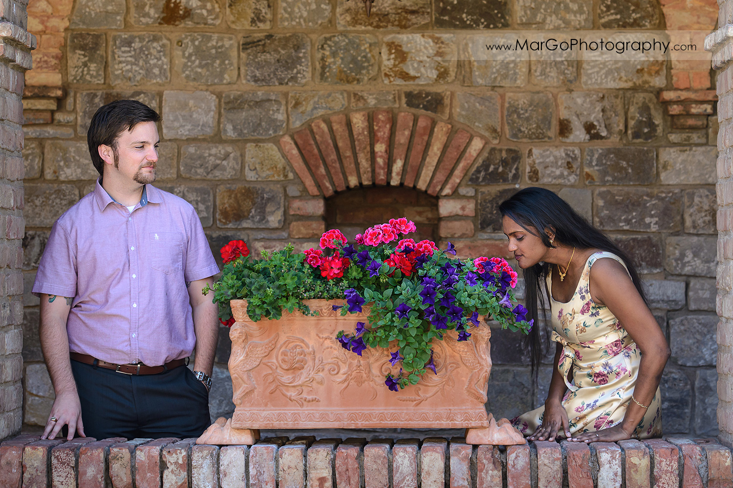man in pink shirt looking at Indian woman in flower dress smelling during engagement session at Castello di Amorosa in Calistoga