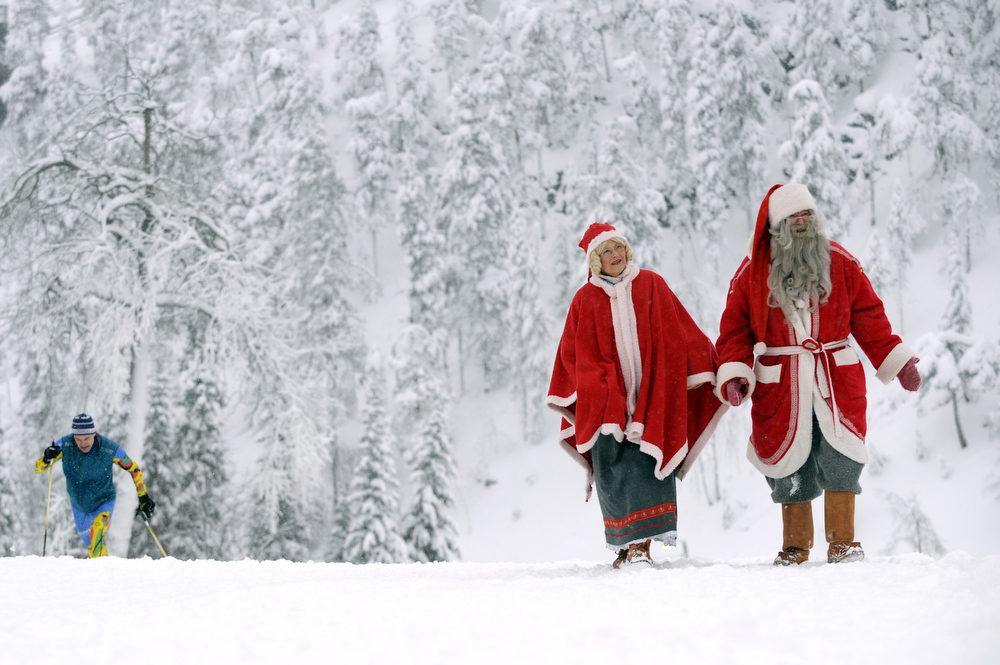 Description of . A couple dressed as Santa Claus walk to the nordic skiing arena as an athlete trains before the World Cup ski jumping team HS 142 on November 28, 2008, in Kuusamo-Ruka .  AFP PHOTO / OLIVIER MORIN