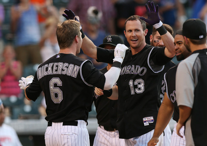 . Colorado Rockies\' Corey Dickerson, left, congratulates teammate Drew Stubbs after his three-run, walkoff home run against the Cincinnati Reds in the ninth inning of a baseball game in Denver on Sunday, Aug. 17, 2014. The Rockies won 10-9. (AP Photo/David Zalubowski)
