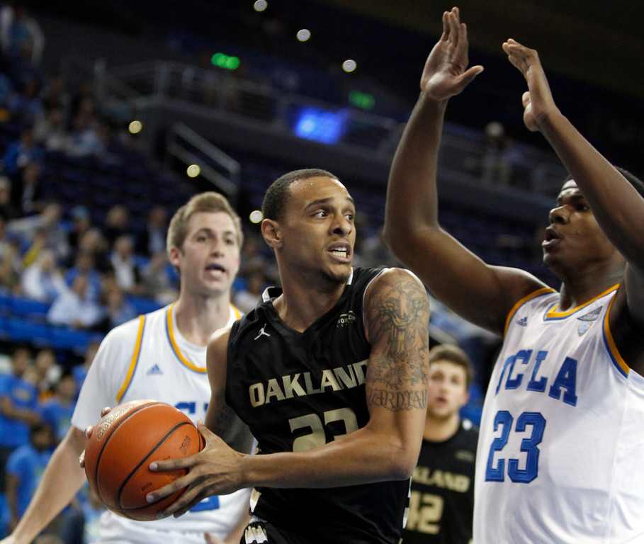 . Oakland forward Tommie McCune, center, looks to pass the ball off with UCLA center Tony Parker, right, and forward David Wear, left, defending in the first half of an NCAA college basketball game Tuesday, Nov. 12, 2013, in Los Angeles. (AP Photo/Alex Gallardo)