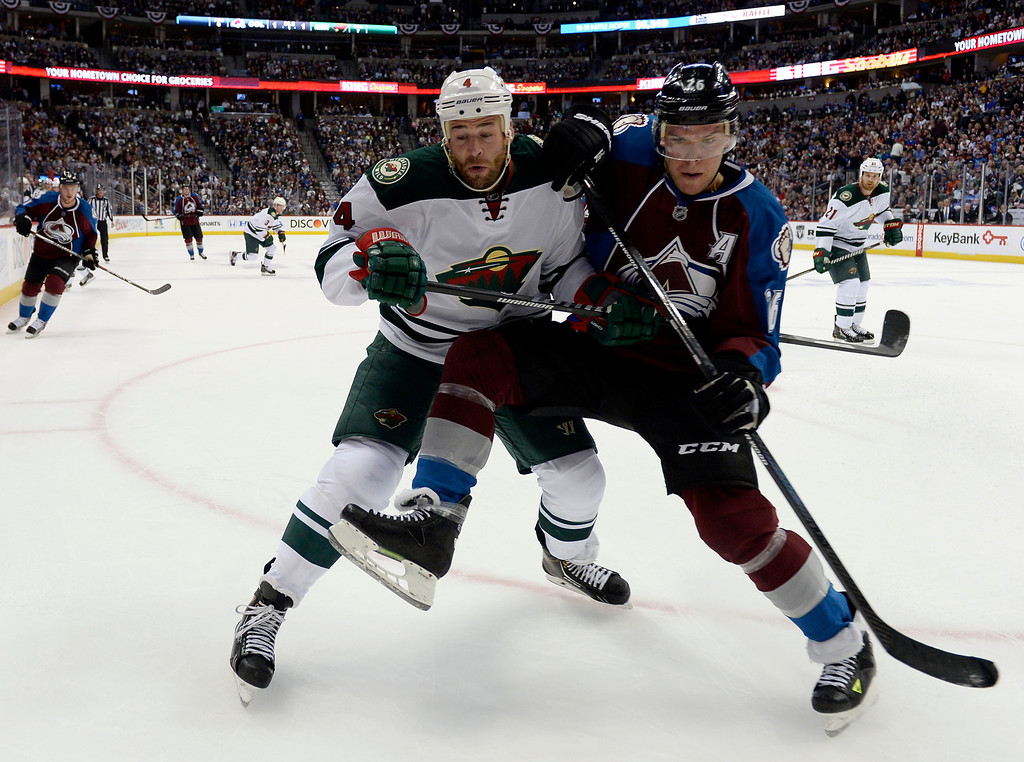 . Paul Stastny (26) of the Colorado Avalanche goes into the boards with Clayton Stoner (4) of the Minnesota Wild during the first period of action. The Colorado Avalanche hosted the Minnesota Wild for the first playoff game at the Pepsi Center on Thursday, April 17, 2014. (Photo by John Leyba/The Denver Post)