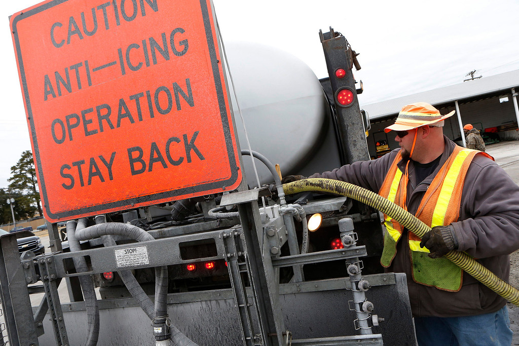 . Kerry Howard refills the brine tank on his truck at the N.C. Division of Highways in Jacksonville, N.C.,Tuesday, Jan. 28, 2014,s to continue brining the roads in the local area as freezing rain and snow approaches.  Snow, sleet and freezing rain are expected across much of North Carolina.     (AP Photo/The Jacksonville Daily News, John Althouse)