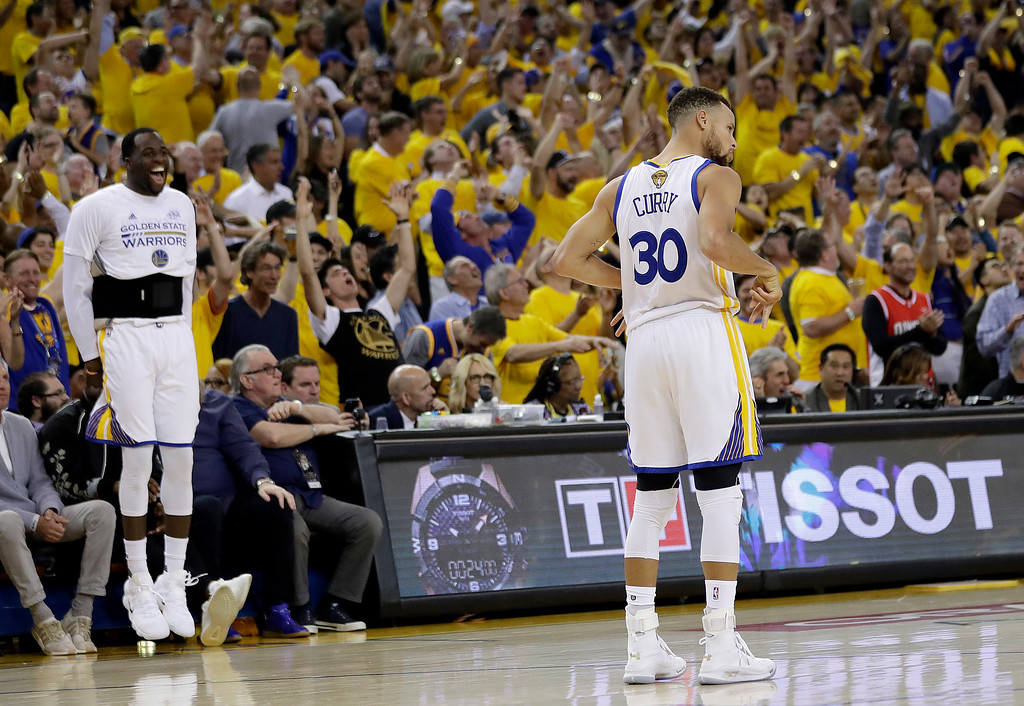 . Golden State Warriors forward Draymond Green, left, and fans cheer after guard Stephen Curry (30) scored against the Cleveland Cavaliers during the second half of Game 2 of basketball\'s NBA Finals in Oakland, Calif., Sunday, June 4, 2017. (AP Photo/Marcio Jose Sanchez)