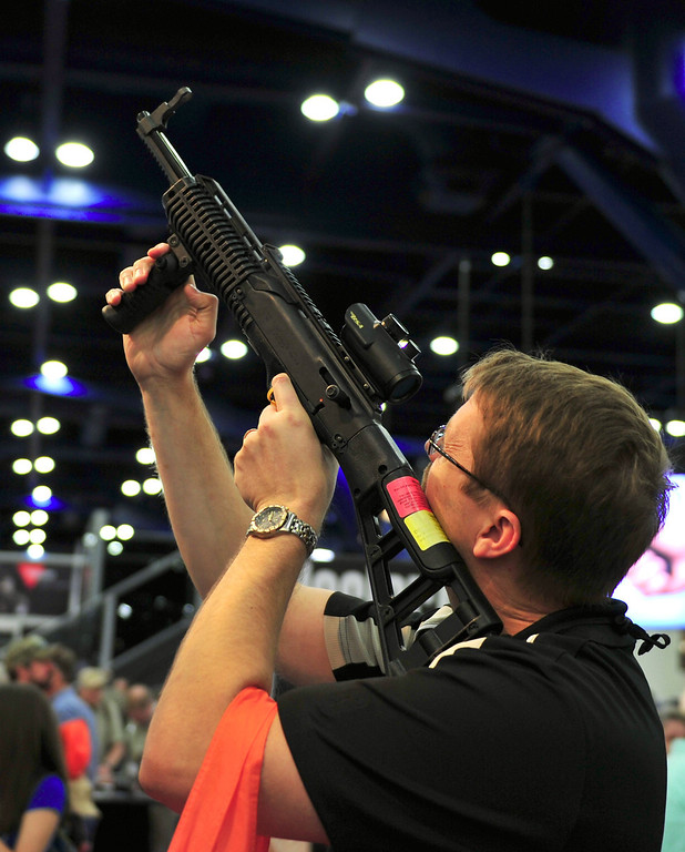 . A man hefts a Hi-Point semi-automatic carbine at the National Rifle Association (NRA) annual Convention annual on May 4, 2013 in Houston, Texas. The National Rifle Association opened its annual convention Friday in combative style, positioning itself as champion of American freedoms in the face of growing pressure for tougher gun laws.  KAREN BLEIER/AFP/Getty Images