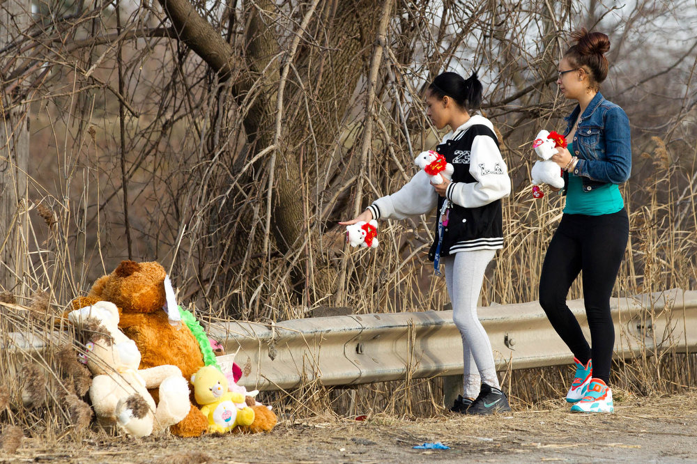. Dominique Ellison, left, and Rickie Bowling, of Warren, bring stuffed animals to a memorial in honor of their friends who died in a car crash on Park Ave. in Warren, Ohio on Sunday, March 10, 2013. (AP Photo/Scott R. Galvin)