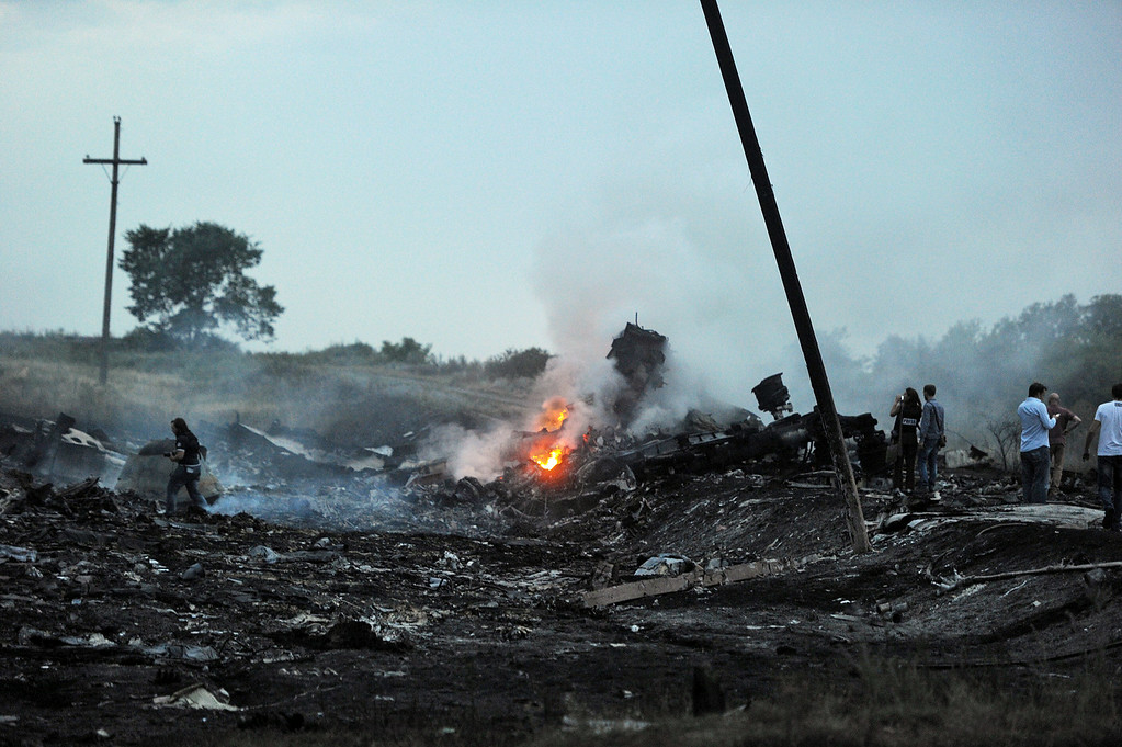 . People stand, on July 17, 2014, amongst the wreckages of the malaysian airliner carrying 295 people from Amsterdam to Kuala Lumpur after it crashed, near the town of Shaktarsk, in rebel-held east Ukraine. Pro-Russian rebels fighting central Kiev authorities claimed on Thursday that the Malaysian airline that crashed in Ukraine had been shot down by a Ukrainian jet. The head of Ukraine\'s air traffic control agency said Thursday that the crew of the Malaysia Airlines jet that crashed in the separatist east had reported no problems during flight. AFP PHOTO/DOMINIQUE FAGET/AFP/Getty Images