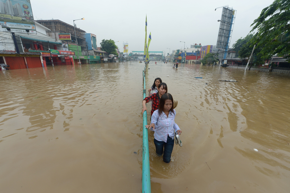 Description of . Indonesian people wade through a flooded street in Jakarta on January 16, 2013. Floodwaters have inundated 52 subdistricts in Jakarta, claiming one life and displacing some 6,000 residents, according to the National Disaster Mitigation Agency (BNPB).  ADEK BERRY/AFP/Getty Images
