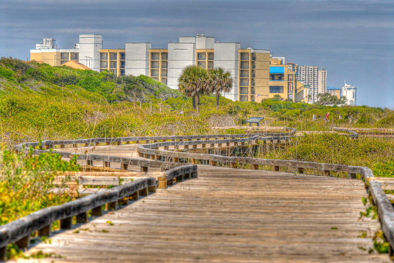 A long oceanfront boardwalk snakes around the park with a view of the hotels beyond in Myrtle Beach State Park in Myrtle Beach, SC on Saturday, April 14, 2012. Copyright 2012 Jason Barnette