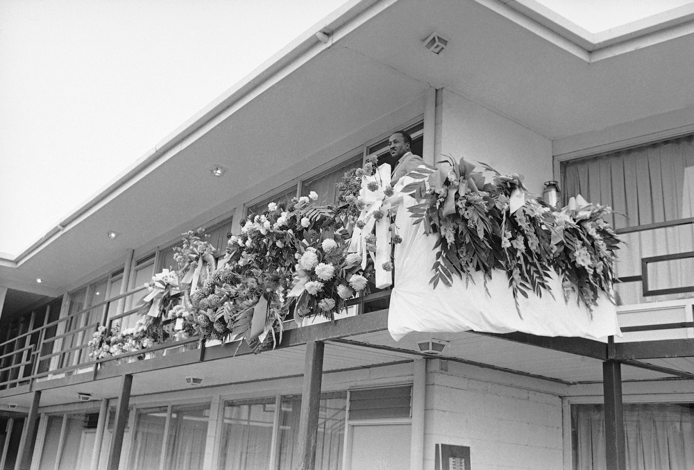 Description of . Floral pieces line the rail outside the room that Dr. Martin Luther King occupied in a motel in Memphis, Tennessee, April 7, 1968. It was outside this room while leaning on the rail that Dr. King was struck and killed by a sniper's bullet on Thursday. An unidentified staff member looks out over the flowers and the direction of the shot.  (AP Photo)