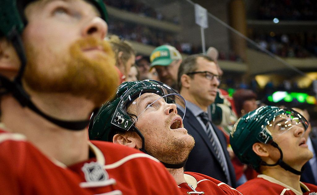 . Minnesota Wild left wing Matt Cooke, center, and other players look at a replay. (Pioneer Press: Ben Garvin)