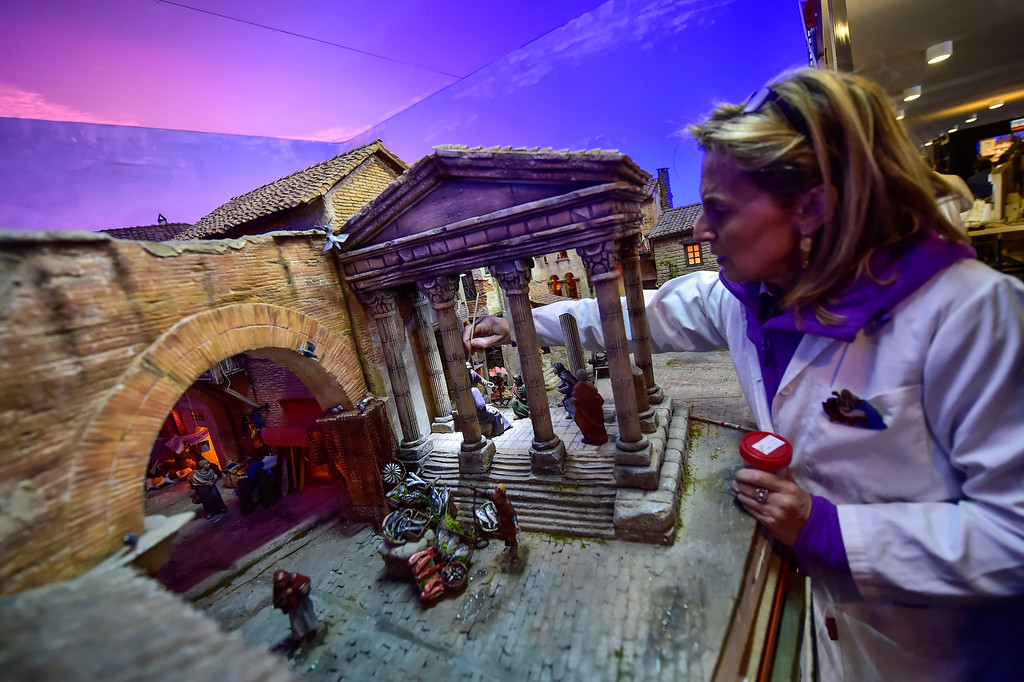 ". In this photo taken on Sunday, Dec. 3, 2017,  Ana Ascunce, a member of a nativity scene group, adds the final touches to a nativity scene, known in Spain as \'\'Belenes\'\', in Pamplona, northern Spain. Spain celebrates the Christmas season with ancient Catholic traditions including the ""Belenes\"", which are handmade from polystyrene and decorated with small nativity figures. AP Photo/Alvaro Barrientos)"