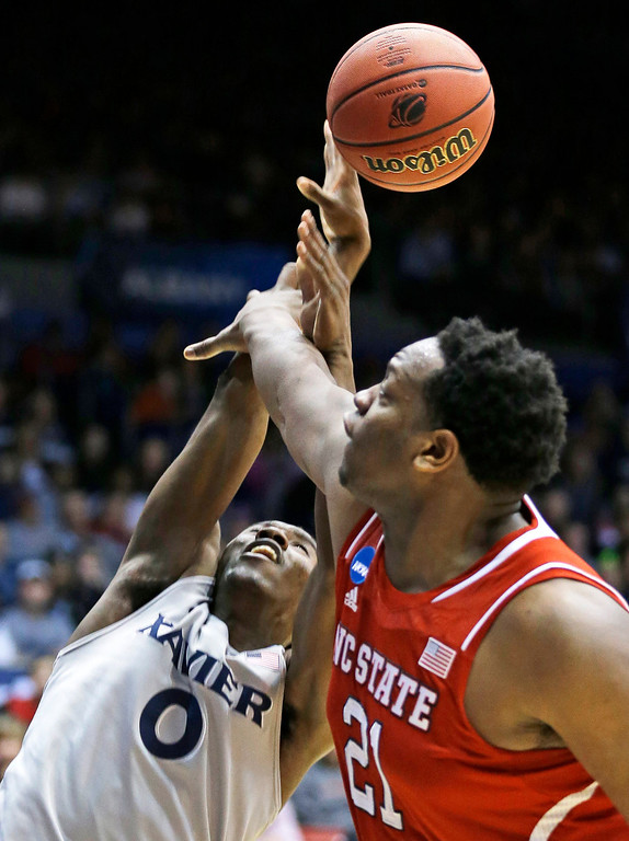 . North Carolina State forward Beejay Anya (21) blocks a shot by Xavier guard Semaj Christon (0) during the first half of a first-round game of the NCAA college basketball tournament, Tuesday, March 18, 2014, in Dayton, Ohio. (AP Photo/Al Behrman)