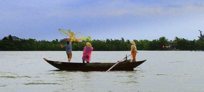 Kent throws a fishing net from the boat