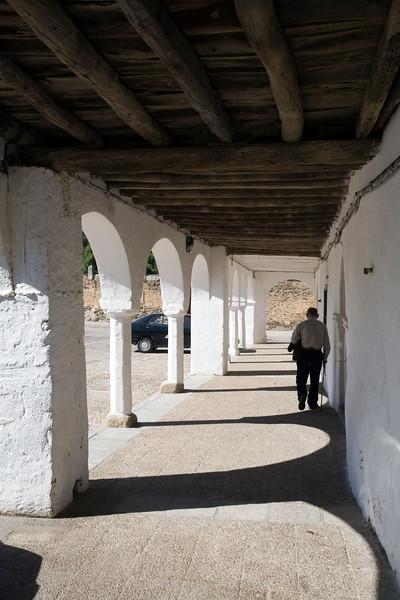 Old man walking under an arcade, main square, Garrovillas de Alconetar, Caceres, Extremadura, Spain