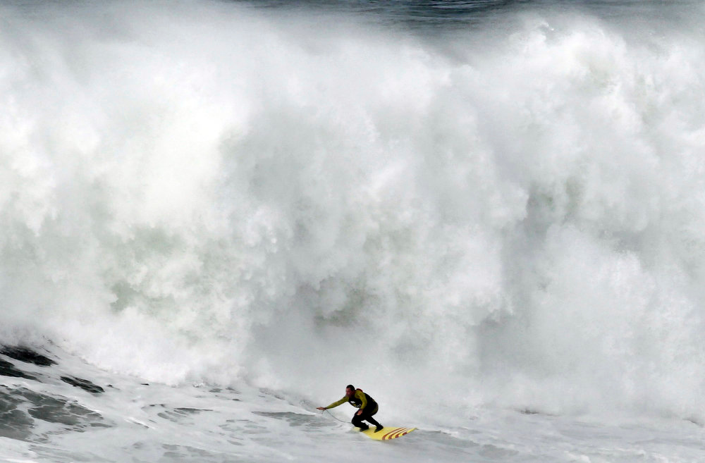 Description of . US surfer Garrett McNanamara rides a wave during a surf session at Praia do Norte beach in Nazare, Portugal, Wednesday, Jan. 30, 2013. McNamara is said to have broken his own world record for the largest wave surfed when he caught a wave reported to be around 100ft, off the coast of Nazare on Monday. If the claims are verified, it will mean that McNamara, who was born in Pittsfield, Massachusetts, USA,  but whose family moved to Hawaii's North Shore when he was aged 11, has beaten his previous record, which was also set at Nazare, of 78 feet in November 2011. (AP Photo/Francisco Seco)